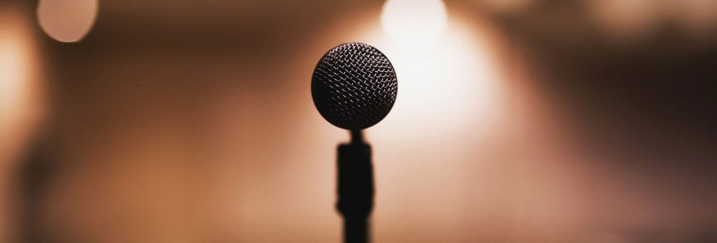 A single microphone on a stage symbolising a fear of public speaking, stage fright, anxiety, and making wedding speeches, by performers, the best man, actors, magicians, comedians, which could easily be treated by hypnotherapy in Wrexham and online